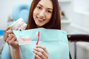 Happy patient with toothbrush | Dentist East Maitland